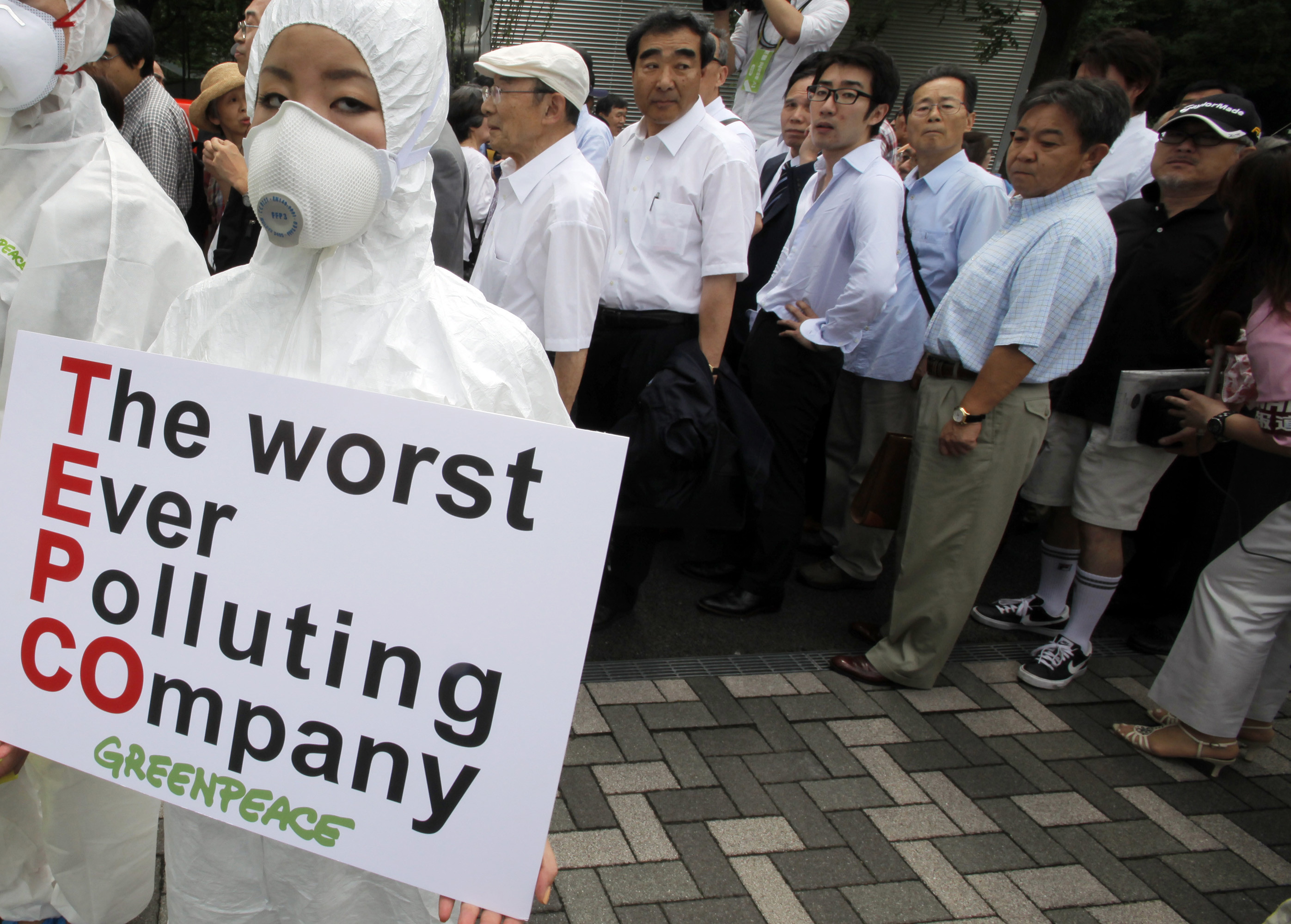 A Greenpeace protester wearing protective gear holds up a banner as stockholders arrive for an annual shareholders' meeting of Tokyo Electric Power Co. in Tokyo in June 2011. | AP