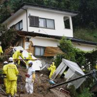Rescue workers on Thursday shift debris after a mudslide struck a home in Kanuma, Tochigi Prefecture. A woman remains missing there. | KYODO