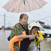 A policeman carries an elderly woman through a flooded street during an evacuation on Thursday morning in Joso, Ibaraki Prefecture, after the nearby Kinugawa River overflowed. | KYODO