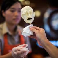 A woman sells an ice cream in the shape of executed Japanese war criminal Hideki Tojo at an ice cream store in Shanghai on Wednesday. | AFP-JIJI
