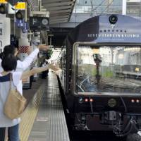 People wave from the platform as Kyushu Railway Co.'s luxury Seven Stars in Kyushu cruise train departs Hakata Station in Fukuoka Prefecture on Aug. 22. | KYODO