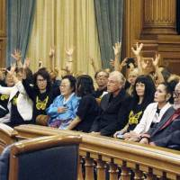Chinese-American and Korean-American residents hail a decision Tuesday at San Francisco City Hall calling for the building of a memorial to 'comfort women.' | KYODO