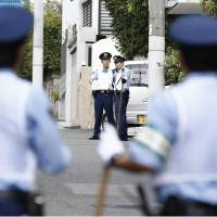 Police officers stand guard in Nada Ward, Kobe, on Tuesday, where the headquarters of the Yamaguchi-gumi crime syndicate is located.   KYODO