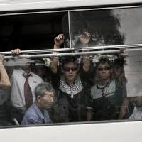 Commuters ride on a city trolley bus Friday in Pyongyang. The North has repeatedly sought to invite the parents of abductee Megumi Yokota to the capital to meet their dranddaughter, but Tokyo has apparently declined the overtures and not informed the parents. | AP