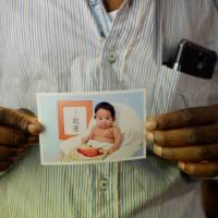 Nosa displays a birth photograph of his son, Ryuma Muratsubaki, who is now 6 years old.   DREUX RICHARD PHOTO