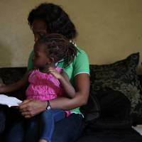 Adaeze, Paul's wife, helps her daughter with homework in their apartment in Lagos.   DREUX RICHARD PHOTO