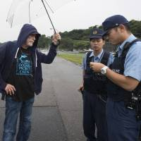 Animal rights activist Ric O'Barry speaks with police officers patrolling the harbor at Taiji, Wakayama Prefecture, on Sept. 9. | ROB GILHOOLY