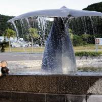 A man and his daughter play with water from a fountain outside the whaling museum in Taiji, Wakayama Prefecture, on Sept. 10, 2009. | ROBERT GILHOOLY