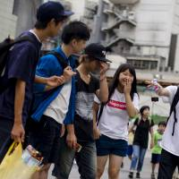 Students Emergency Action for Liberal Democracy co-founder Aki Okuda talks to supporters in Tokyo on Aug. 24. | REUTERS