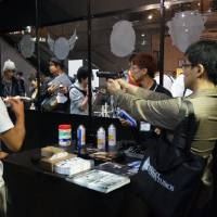 Fear the walking gamers: Tokyo Game Show attendees partake in a shooting range that targets zombies as part of Capcom's promotional 'Biohazard' section. | JASON COSKREY