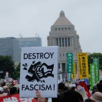 Youth against fascism: A protester holds up a sign during a demonstration in front of the Diet building in Tokyo on Aug. 30. | JEFF KINGSTON