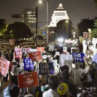 On the march: Protesters gather outside the Diet building last month. Many of the people who took part in this demonstration against the government's security resolutions were students with liberal arts backgrounds. | KYODO