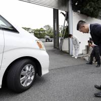 The gang's all here: A man greets a car as it pulls into Yamaguchi-gumi headquarters in Kobe. The weeklies have been speculating on the outcome of a split within the group's membership that could result in anything from a war to 'mutual coexistence.' | KYODO