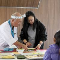 Chef Hidekazu Tojo shows an Inuit woman how to make sushi during our Arctic cruise in July. | YOICHI YABE