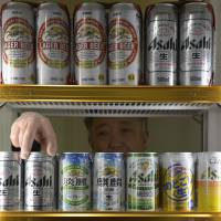The taxman cometh: A liquor shop owner fills a fridge with beer and its cheaper low-malt cousins in Kawasaki. | BLOOMBERG