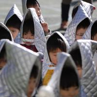 Kindergarten students sit in a playground wearing bōsai zukin during an earthquake drill at an elementary school in Tokyo on March 11, 2014. | REUTERS