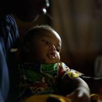 Andy holds his son, Jason, during a power outage in Onitsha, Anambra State, in southeastern Nigeria.   DREUX RICHARD