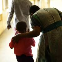 Emanuel's younger son talks to a teacher at his elementary school in Benin City.   DREUX RICHARD