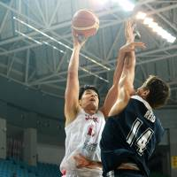 Japan's Joji Takeuchi takes a shot over Hong Kong's Duncan Overbeck Reid during a FIBA Asia Championship match on Tuesday in Wuhan, China. Takeuchi scored 17 points in Japan's 89-62 triumph. KYODO | KYODO