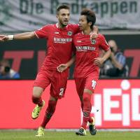 Hannover's Hiroshi Kiyotake (right) celebrates with teammate Kenan Karaman after scoring against Wolfsburg on Saturday. | AP