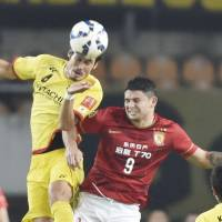 Kashiwa defender Daisuke Suzuki (left) vies for the ball with Guangzhou forward Elkeson during their Asian Champions League quarterfinal match on Tuesday in Guangzhou, China. | KYODO