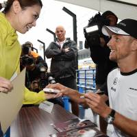 McLaren driver Jenson Button shakes hands with a fan on Thursday during a meet-and-greet event before Sunday's Formula One Japanese Grand Prix in Suzuka, Mie Prefecture. | AFP-JIJI