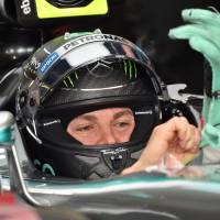 Mercedes driver Nico Rosberg fits his gloves before the third practice session of the Formula One Japanese Grand Prix at the Suzuka Circuit on Saturday. | AFP-JIJI