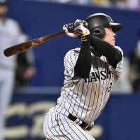 The Tigers' Kosuke Fukudome slaps a run-scoring single with two outs in the eighth inning against the Dragons on Friday at Nagoya Dome. Hanshin defeated Chunichi 3-0. | KYODO