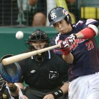 Tetsuto Yamada hits an RBI double in the seventh inning of the Swallows' 5-2 win over the Tigers at Koshien Stadium on Monday. | KYODO