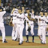 Tokyo Yakult players celebrate their 6-2 win over the Dragons on Monday night at Jingu Stadium. | KYODO