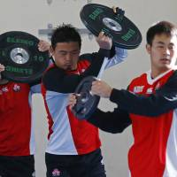 Japan's Ayumu Goromaru (center) and two teammates work out with weights on Tuesday in Warwick, England. | REUTERS