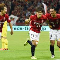 Reds' Yoshiyuki Takagi  (center) celebrates his game-winning goal against Reysol with teammates Tomoya Ugajin (3) and Tomoaki Makino on Friday night in Saitama. Urawa defeated Kashiwa 1-0. | KYODO