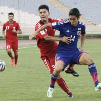 Japan's Yoshinori Muto vies for the ball with Afghanistan's Hassan Amin during their World Cup qualifier on Tuesday. | KYODO