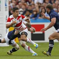 Japan's Yu Tamura tries to break through the Scotland defense during their Rugby World Cup match last week. | REUTERS
