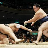 Yokozuna Kakuryu shoves down Osunaarashi during their bout on Wednesday. | KYODO
