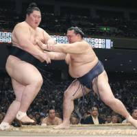 Yokozuna Kakuryu grapples with No. 2 maegashira Sadanoumi on Saturday, the seventh day of the Autumn Grand Sumo Tournament at Ryogoku Kokugikan. Kakuryu improved to 6-1. | KYODO