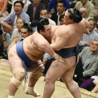 Kotoshogiku (left) outmuscles Kisenosato en route to victory on Tuesday at the Autumn Grand Sumo Tournament. | KYODO