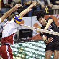 Kunihiro Shimizu spikes the ball past two Poland defenders on Tuesday during the FIVB Men's Volleyball World Cup in Tokyo. Unbeaten Poland defeated Japan  24-26, 27-25, 25-21, 25-19. | KYODO
