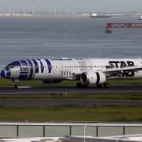 An All Nippon Airways Boeing 787-9 painted in a Star Wars theme based on the droid R2-D2, lands at Tokyo's Haneda airport on Friday. | AFP-JIJI