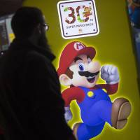A visitor walks past a Super Mario logo at a Nintendo Co. stand at the EGX 2015 video game conference in Birmingham, England, in September. Nintendo has been dropped for the first time from U.S.-based Interbrand's list of the top 100 global brands. | BLOOMBERG