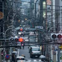 Power and utility cables strung from poles crisscross a shopping street in Hachioji in Tokyo. The government is promoting liberalization of the electricity market to reduce costs and increase grid reliability for consumers. | BLOOMBERG