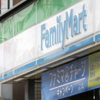 Signs for FamilyMart Co. and Sunkus convenience stores are displayed in Tokyo in March. The operator of Sunkus is Uny Group Holdings Co. | BLOOMBERG