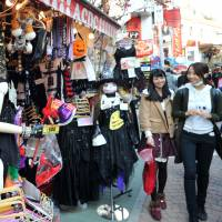 Pedestrians pass a store packed with Halloween costumes on trendy Takeshita-dori in Tokyo's Harajuku district on Friday. Businesses have been increasingly importing the commercial version of an ancient spiritual and religious festival. | YOSHIAKI MIURA