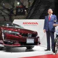Honda Motor Co. President Takahiro Hachigo presents the hydrogen-powered Clarity Fuel Cell sedan at the Tokyo Motor Show, which opened Wednesday at the Tokyo Big Sight exhibition center in the city's Koto Ward. | YOSHIAKI MIURA