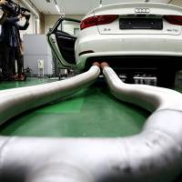 Members of media film an Audi AG A3 35 TDI emissions certification vehicle, produced by Volkswagen AG, waiting to be tested inside the Transportation Pollution Research Center laboratory, operated by National Institute of Environmental Research in Incheon, South Korea, on Thursday.  | BLOOMBERG