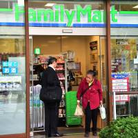 Customers walk near a FamilyMart convenience store in Tokyo on Thursday. FamilyMart Co. will merge with Uny Group Holdings Co. next year to become the nation's third-largest retail group. | AFP-JIJI