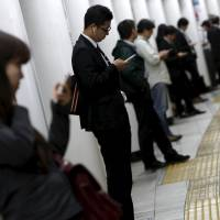 People look at their mobile phones while waiting for a train at a subway station in Tokyo on Oct. 14. | REUTERS