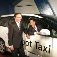Kanagawa Gov. Yuji Kuroiwa (left) and Shinjiro Koizumi, parliamentary vice minister of the Cabinet Office, pose with an experimental self-driving car developed by Robot Taxi Inc., on Thursday in Yokohama. | KAZUAKI NAGATA