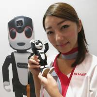 A model shows off Sharp Corp.'s RoBoHoN, a phone combined with a humanoid robot, at the CEATEC trade fair in the city of Chiba on Tuesday. | KAZUAKI NAGATA