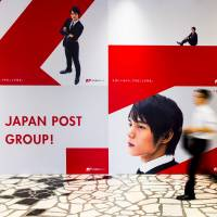 A man walks past a Japan Post Holdings Co. ad at its headquarters in Tokyo in June. | REUTERS